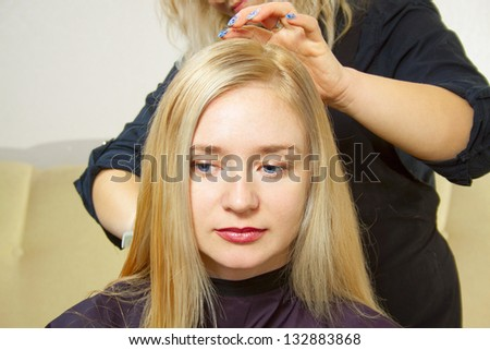 Hairdresser giving a new haircut to young female - stock photo