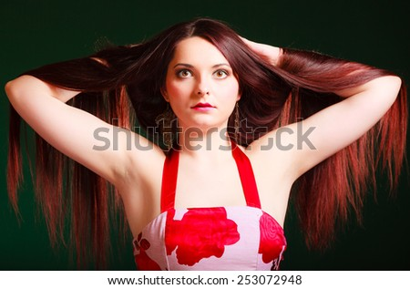 Hairdresser, hairstylist and haircare. Long haired beauty woman creating coiffure. Studio shot on green background. - stock photo