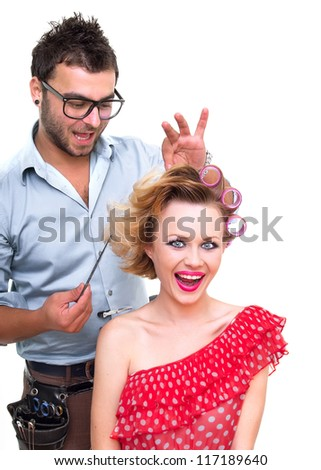 Hairdresser make a hairstyle for woman, isolated on white - stock photo