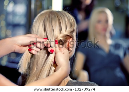 Hairdresser make French braids   in beauty salon. - stock photo