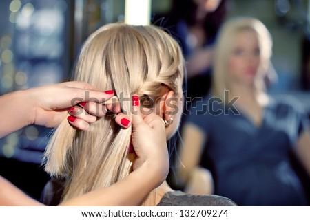 Hairdresser make French braids   in beauty salon.