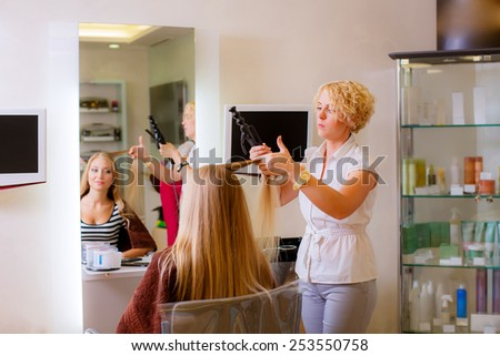 Hairdresser makes hair beautiful girl in a beauty salon - stock photo