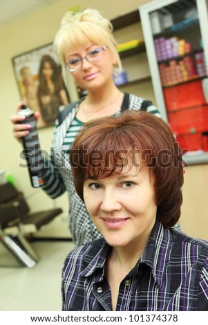 Hairdresser makes hair styling for woman by hair spray in beauty salon; focus on happy client - stock photo