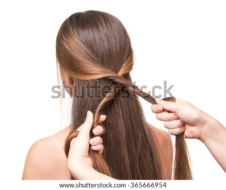 Hairdresser makes hairstyle girl long straight hair, isolated on white background - stock photo