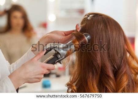 hairdresser bing her long red hair stock photo