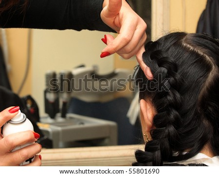 Hairdresser makes hairstyle on the long black hair woman - stock photo