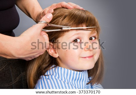 Hairdresser making a hair style to cute little girl - stock photo