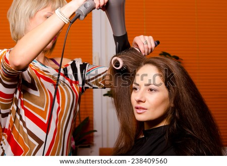 Hairdresser making hair of beautiful happy girl.