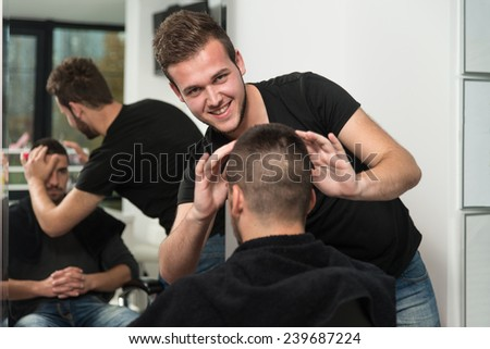 Hairdresser Preparing Young Man After A New Haircut - stock photo
