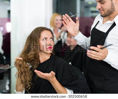 Hairdresser quarrels with the female client in the barbershop - stock photo