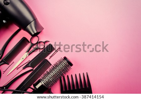 Hairdresser set with various accessories on pink background - stock photo
