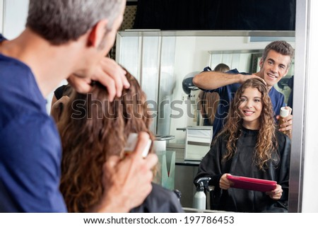 Hairdresser setting up client's hair while looking at mirror in salon