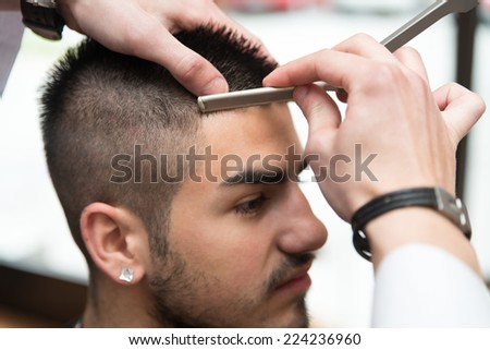 Hairdresser Shaving Man's Forehead With A Straight Razor - Handsome Young Hairdresser Giving A New Haircut To Male Customer At Parlor - stock photo