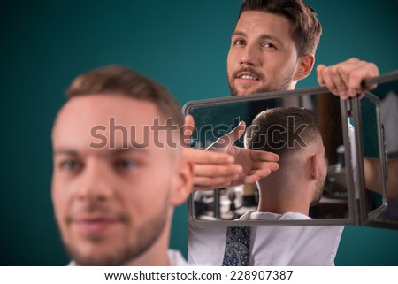 hairdresser  shows  short haircut with mirror to handsome satisfied  client in  professional  hairdressing salon