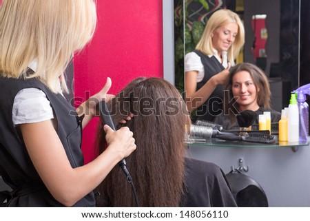 hairdresser straightening woman's hair with iron in beauty salon - stock photo