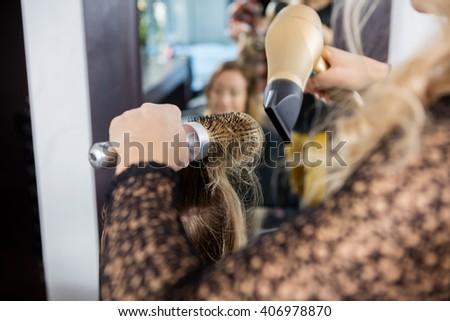 Hairdresser Styling Female Customer's Hair In Salon - stock photo
