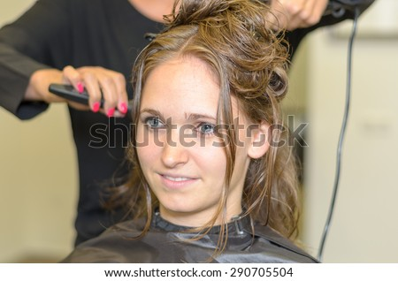 Hairdresser styling the long hair of an attractive young woman in her hairdressing salon, close up of the young clients smiling face - stock photo