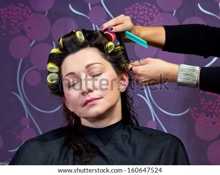 hairdresser stylist putting rollers in mature woman hair in salon