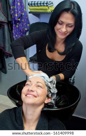 hairdresser stylist washing woman hair in salon - stock photo