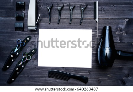 Hairdresser tools on wooden background. Blank card with barber tools flat lay. Top view on wooden table with scissors, comb, clipper and hairdryer with empty white paper, free space