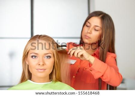 Hairdresser uses hair straightener. - stock photo
