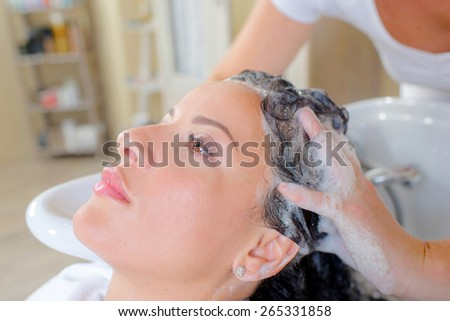 Hairdresser washing a woman's hair - stock photo