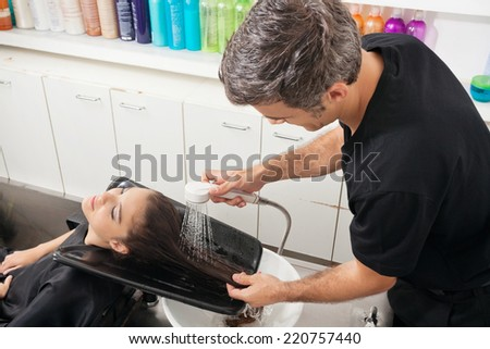 Hairdresser washing female client's hair in beauty parlor - stock photo