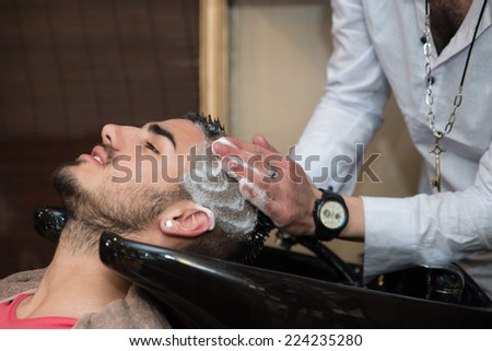 Hairdresser Washing Man Head In Barber Shop - Hairstylist Hairdresser Washing Customer Hair - Young Man Relaxing In Hairdressing Beauty Salon - stock photo