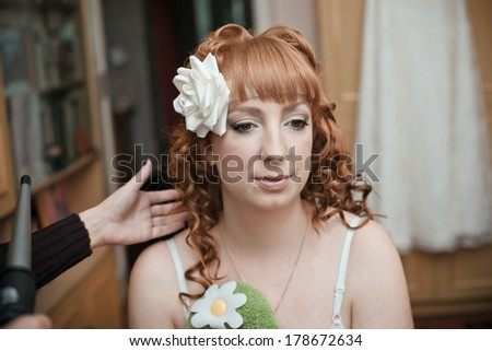Hairdresser with a client at beauty salon. girl doing hairstyle. charges bride