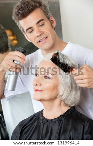 Hairdresser with spray and brush setting up female client's hair - stock photo