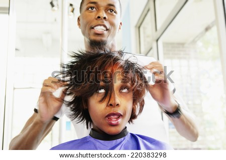 Hairdresser working on young woman's hair - stock photo