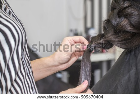 Hairdresser working with beautiful woman hair in hairdressing salon. Close up view of hands