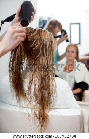 Hairdressers hands drying long blond hair with blow dryer at parlor - stock photo