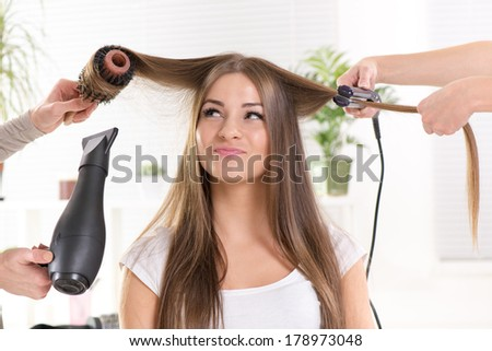 Hairdressers straightening long brown hair with hair dryer and round brush and hair irons. - stock photo
