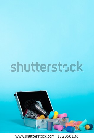 Hairdressing. Hair accessories tools hairdryer colorful curlers in suitcase. Copy space for text. Vivid blue background - stock photo