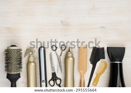 Hairdressing tools on wooden background with copy space at top - stock photo