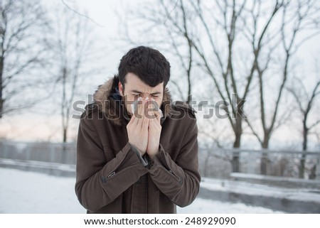 haired bearded man Blowing His Nose  in winter park - stock photo