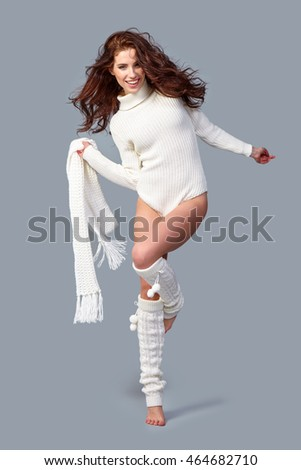Haired beautiful woman in winter clothes on a gray isolated background,