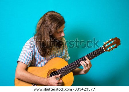 haired man playing classical acoustic guitar
