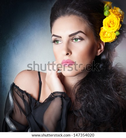 Hairstyle and Make up - beautiful female art portrait with yellow roses.Elegance. Genuine Natural brunette with Flowers. Portrait of a attractive woman with beautiful eyes and flowers in her hair.  - stock photo