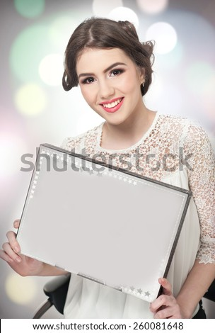 Hairstyle and make up - beautiful young girl holding a white paper in her hands. Genuine natural brunette, studio shot. Attractive female with beautiful lips and eyes in white lace blouse, over white - stock photo