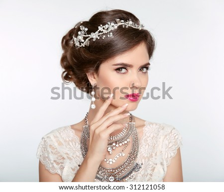 Hairstyle. Attractive girl with makeup. Jewelry Earring. Expressive eyes stare. Elegant lady isolated on studio white background. Luxury style.