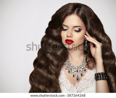 Hairstyle. Healthy hair. Makeup. Beautiful brunette girl with long wavy hair style and Red lips. Elegant lady with luxury expensive pendant jewelry. Wedding.  - stock photo