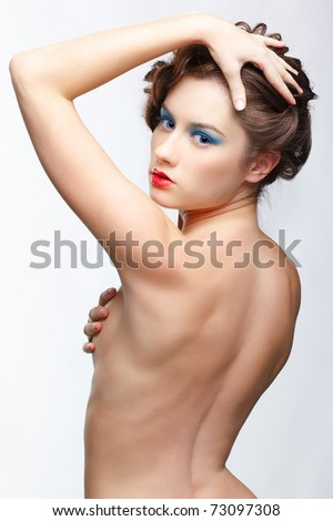 hairstyle portrait of beautiful brown-haired girl with creative hairdo standing back to camera