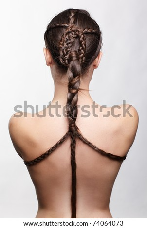 hairstyle portrait of beautiful brunette girl with creative braid hairdo standing back to camera