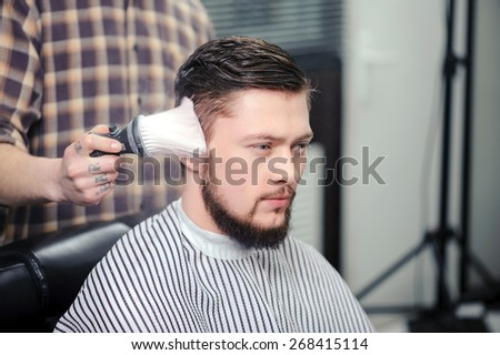 Hairstyling. Close-up of a barber touching with a brush haircut of a male client - stock photo