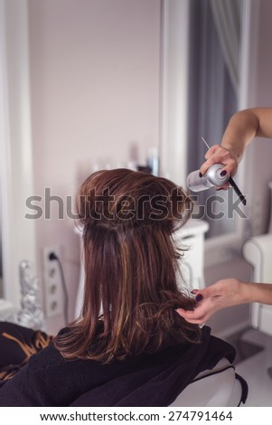 Hairstylist applying hair spray while arranging it - stock photo