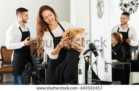 Hairstylist cuts young woman's hair in the barbershop