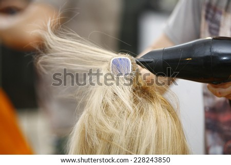 Hairstylist Drying Hair Blonde in Salon for short hair - stock photo