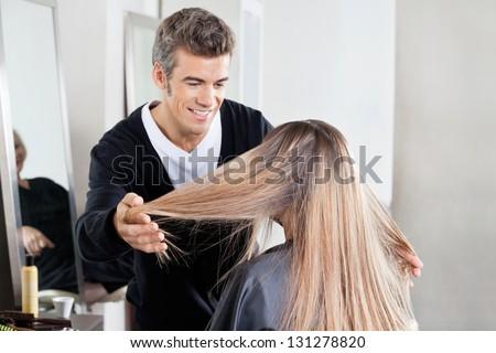 Hairstylist examining female client's hair at hair salon - stock photo